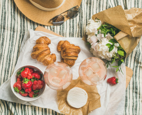 French style summer outdoor picnic setting. Flat-lay of glasses with rose wine, strawberries, croissants, brie cheese on board, hat, sunglasses, peony flowers, top view. Outdoor gathering concept